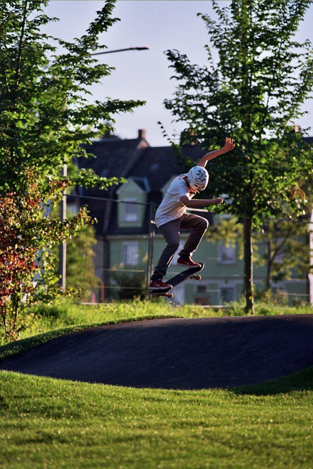 Ollie mit Skateboard über Pumptrack