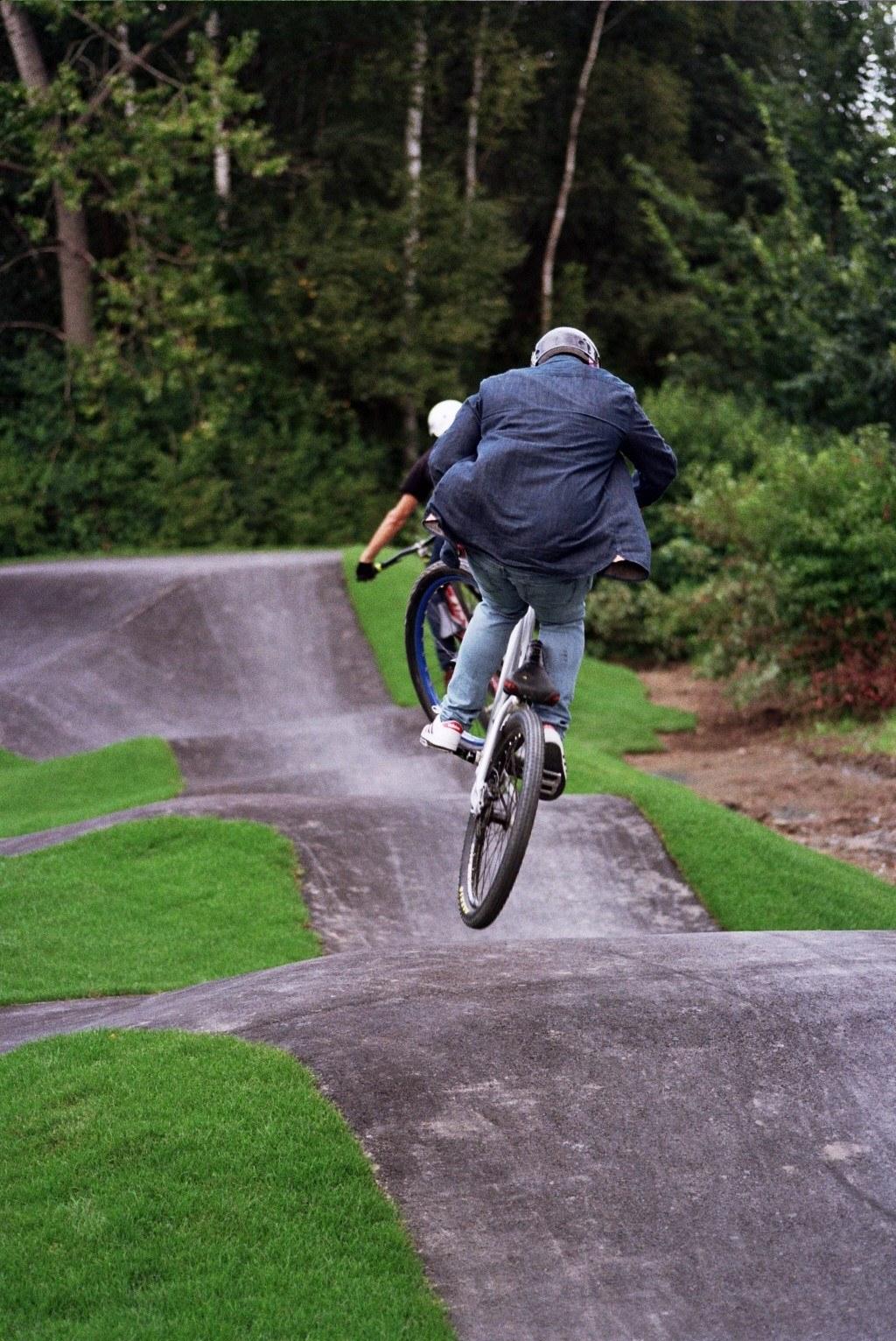 Springender Fahrradfahrer auf Pumptrack gebaut von Radquartier!