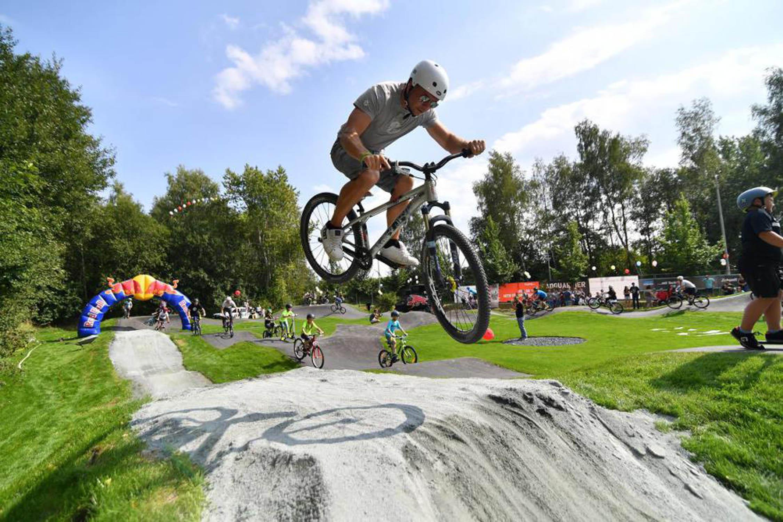 Junger Mann springt bei Pumptrack Eröffnung über Dirtjump