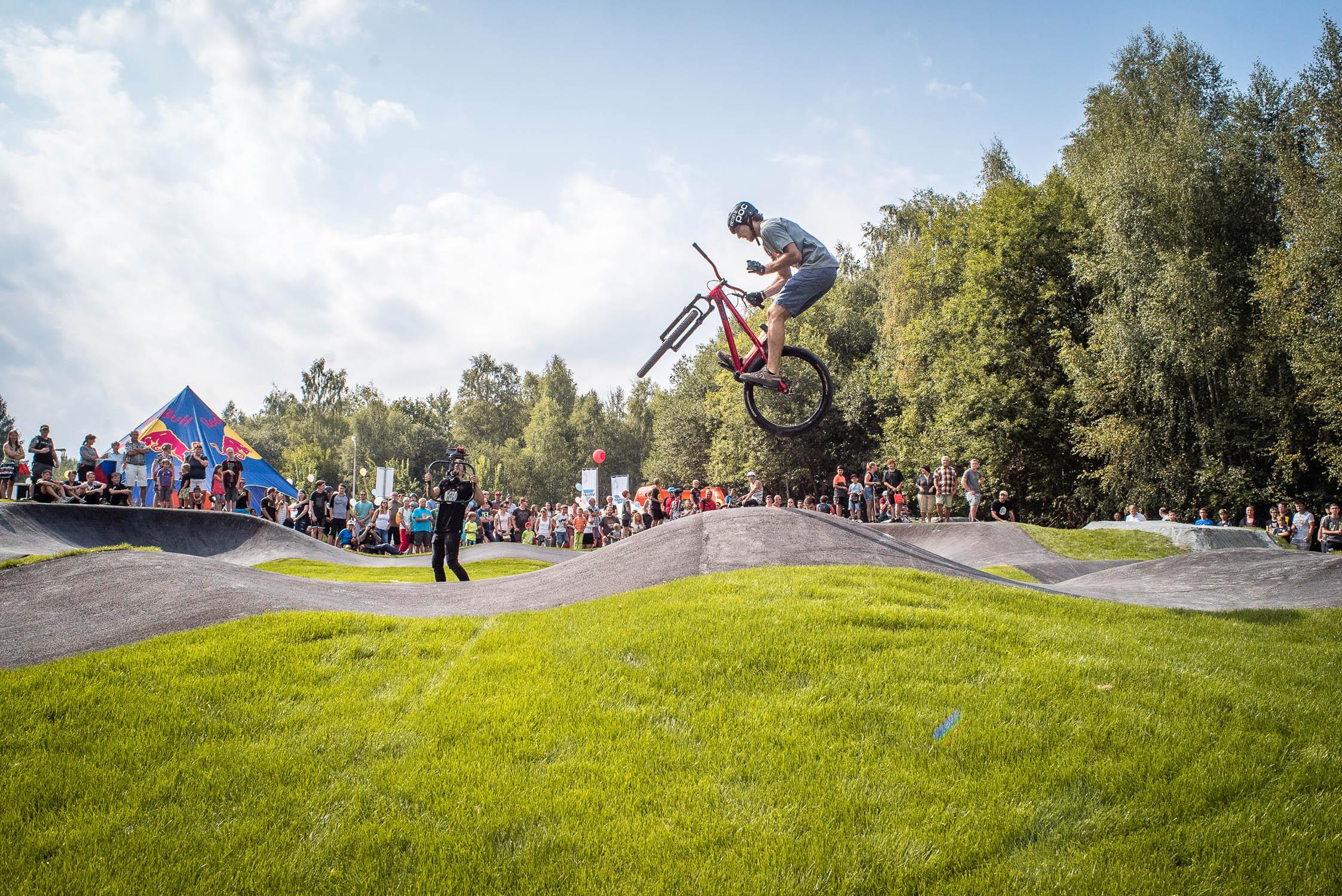Mountainbiker macht Trick über Pumptrack.