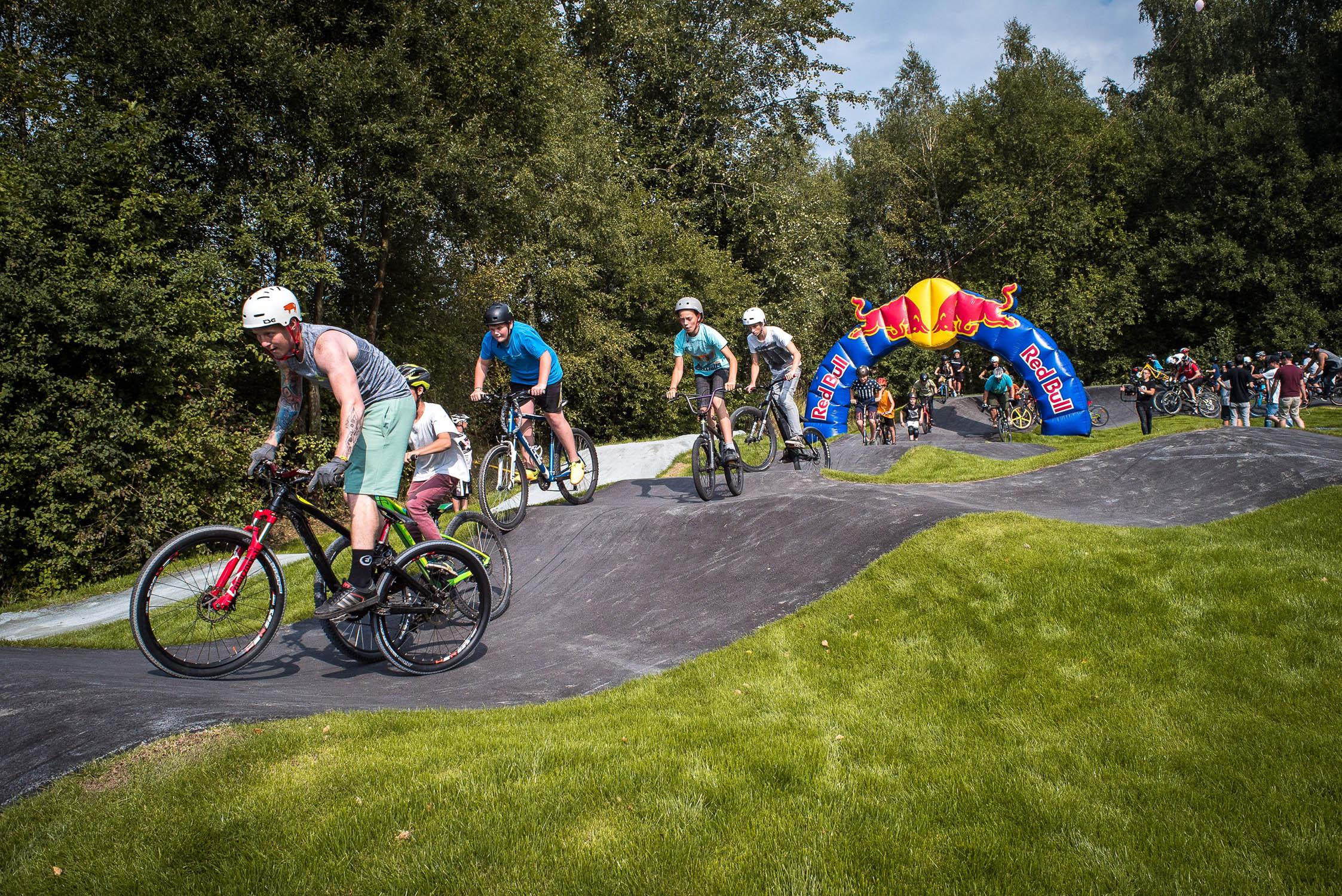 Mountainbiker, Scooter und BMX-Fahrer fahren durch RedBull-Torbogen