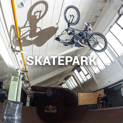 Mann macht Trick mit BMX in Skatepark