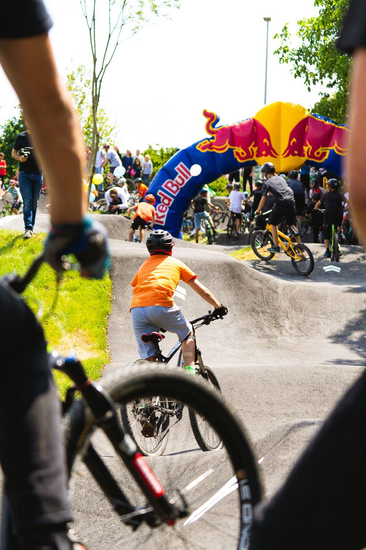 Jung und Alt fahren zusammen Mountainbike und Bmx auf der asphaltierten Pumptrack Bahn in Litzendorf. RadQuartier GmbH